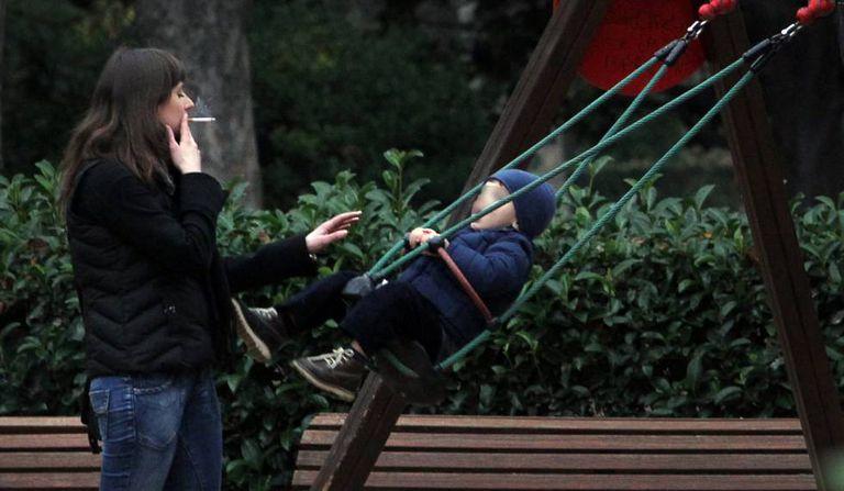 Mulher fuma um cigarro diante de uma criança.