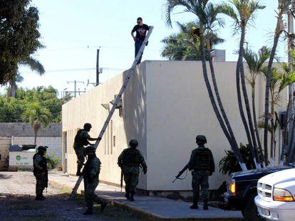 Um grupo de soldados vistoria o telhado no qual foi encontrado o corpo supostamente atirado de um pequeno avião.