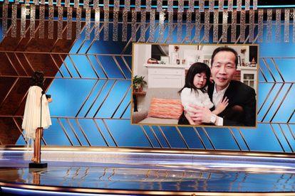 Lee Isaac Chung recebe de maneira virtual, com sua filha nos braços, o Globo de Ouro.