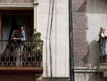 Vizinhos conversam pela sacada em um prédio em Madri.