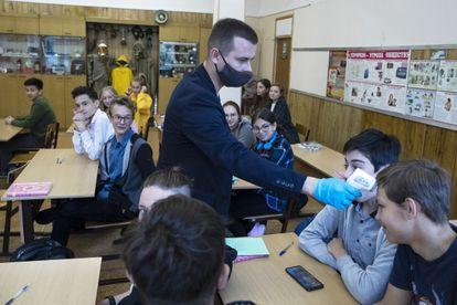 Professor mede a temperatura de um aluno em Moscou, em 7 de setembro.