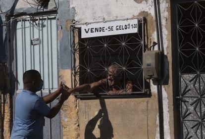 Agente de saneamento cumprimenta morador que vende gelo no Complexo da Maré, no Rio.