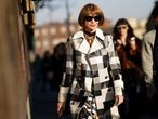 MILAN, ITALY - FEBRUARY 21: Anna Wintour wears sunglasses, a bejeweled necklace, a black and white checkered long trench coat, a floral print dress, outside Marni, during Milan Fashion Week Fall/Winter 2020-2021 on February 21, 2020 in Milan, Italy. (Photo by Edward Berthelot/Getty Images)