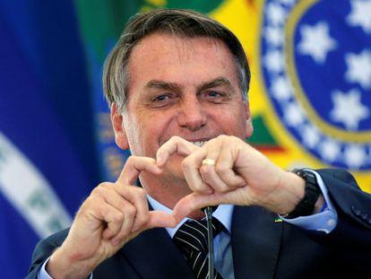 O presidente Jair Bolsonaro faz sinal de coração em evento sobre programa da Caixa Econômica Federal em Brasília.