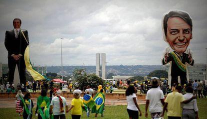 Seguidores do presidente Jair Bolsonaro caminham na frente de um boneco gigante com sua figura em Brasília.