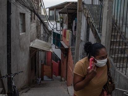 Uma mulher com uma máscara fala ao telefone em Paraisópolis, em São Paulo, no último 6 de maio.