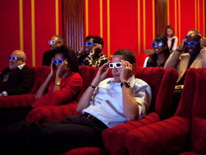 Os Obama assistem um anúncio em 3D na sala de cinema da Casa Branca.
