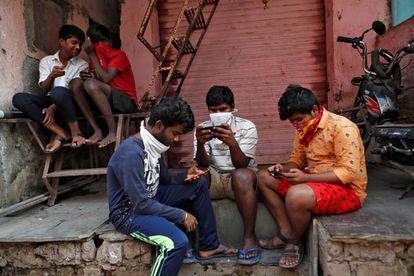 Um grupo de jovens checa seus celulares em Bombaim.