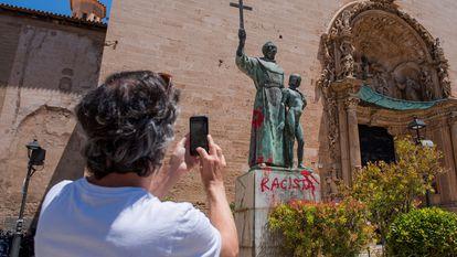 Um homem fotografa uma pichação crítica no monumento dedicado ao frade Junípero Serra em Palma de Mallorca, em 22 de junho de 2020.