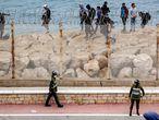 Agentes de seguridad marroquíes montan guardia mientras un grupo de migrantes caminan por la costa en la ciudad norteña de Fnideq, en un intento de cruzar la frontera de Marruecos al enclave español de Ceuta, este martes.