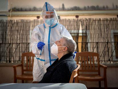 Profissional de saúde faz teste de covid-19 em residente de lar de idosos em Barcelona.