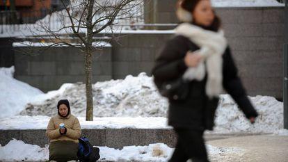 Mulher pede dinheiro em uma rua de Helsinki, em janeiro de 2010.