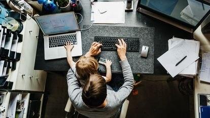 Uma mãe trabalha em 'home office' com sua filha no colo.