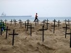 A man runs past the one hundred graves which were dug by activists of the NGO Rio de Paz on Copacabana beach symbolising the dead from the coronavirus disease (COVID-19), in Rio de Janeiro, Brazil, June 11, 2020. REUTERS/Pilar Olivares