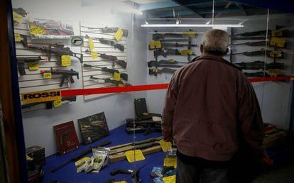 Homem observa vitrine com armas em São Paulo.