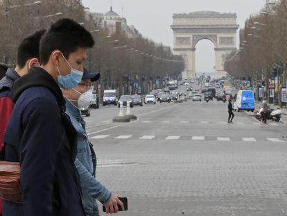 Turistas usam máscaras de proteção na avenida Champs Elysees, em Paris, no dia 17 de março.