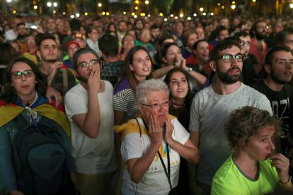 Manifestantes pró-independência acompanham o discurso de Puigdemont do lado de fora do Parlamento da Catalunha.