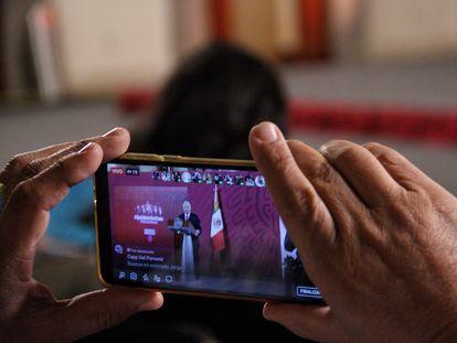 Uma pessoa grava com seu celular a entrevista coletiva do presidente do México, Andrés Manuel López Obrador.