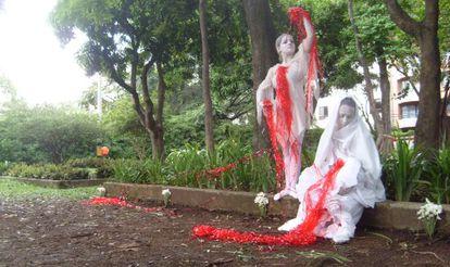 Dois atores da fundação Alas de Mariposa recriam a Pietà como esculturas humanas numa intervenção no Parque da Bailarina de Medellín.
