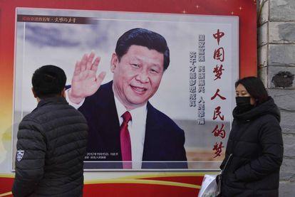 Duas pessoas passam diante de um cartaz com a foto do presidente Xi Jinping em Pequim, nesta segunda-feira.