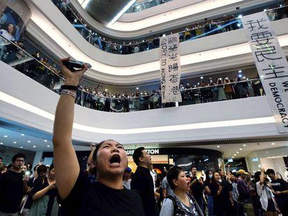 Manifestantes pró-democracia se reúnem em um shopping center de Hong Kong para cantar o hino.