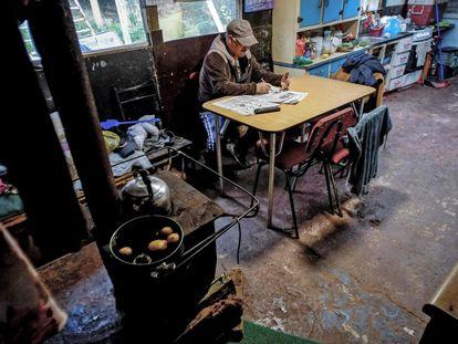 Um homem de 63 anos se senta na cozinha de sua casa no acampamento Pedro del Río Zanartu em Concepción, Chile.