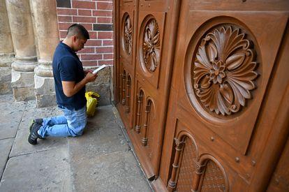 Homem reza às portas da Basílica do Senhor dos Milagres na Colômbia.