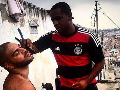 Adriano faz a barba em uma rua da Vila Cruzeiro.