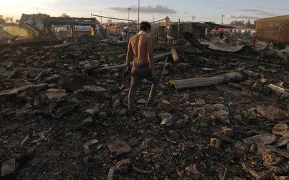 Homem caminha entre os escombros, após a tragédia.