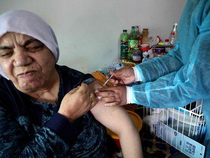 Enfermeira palestina aplica dose da vacina Comirnaty Pfizer-BioNTech na vila de Dura, próximo a Hebron, na Cisjordânia.