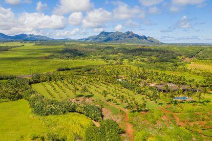 Panorâmica do gigantesco terreno na ilha de Kauai. Tudo é verde de um lado, e azul-marinho no outro. Se o dono quiser dar uma festa, ninguém se queixará à noite.