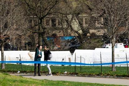 Jovens tiram foto perto do hospital de campanha erguido no Central Park, em Nova York.