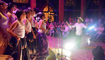 Sebastián Velasquez e os jovens de coral Chaminade dão um concerto de música colombiana para a comunidade do bairro Santo Domingo Savio.