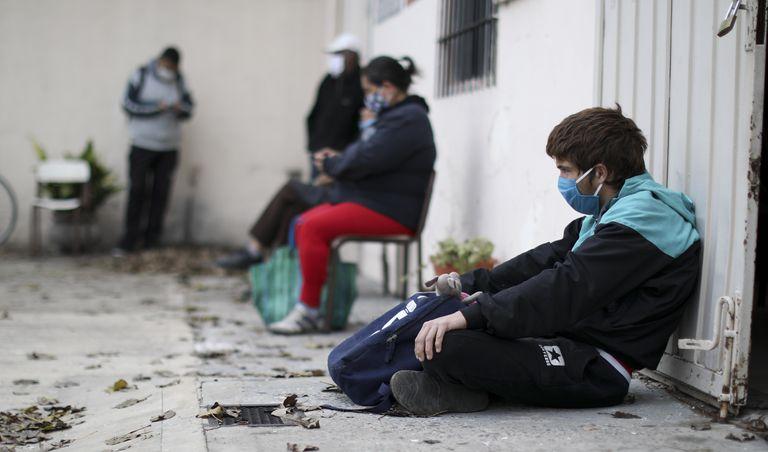 Um grupo de pessoas espera na porta de uma igreja em Buenos Aires que funciona como refeitório social.