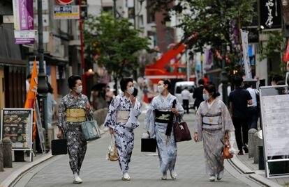 Mulheres passeiam em Tóquio com o traje tradicional de gueixa, em julho.