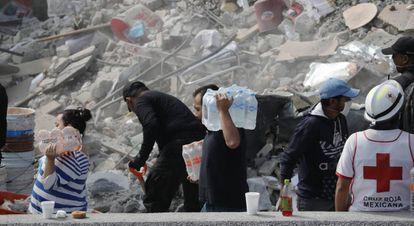 Pessoas levam água e alimentos aos locais onde brigadistas e voluntários fazem os trabalhos de resgate.