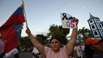 Mulher segura a bandeira da Venezuela em um protesto contra a morte em um naufrágio de migrantes venezuelanos em 17 de dezembro.