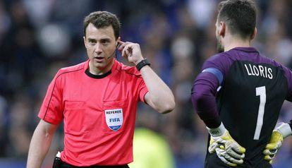 O árbitro da partida entre França e Espanha se comunica com os assistentes.