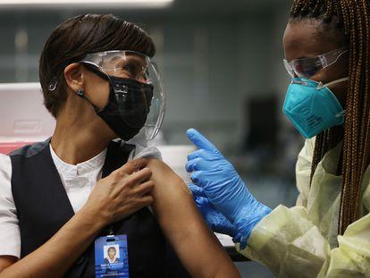 Funcionária da Aeroméxico recebe uma vacina da Pfizer no Aeroporto Internacional de Miami, em maio de 2021.