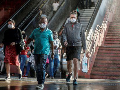 Usuário passam por cabine de desinfecção em estação de metrô de Osasco (SP).
