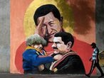A man walks past a mural depicting Venezuelan late President Hugo Chavez (C) saluting and Venezuelan President Nicolas Maduro (R) holding a child in Caracas on December 9, 2020. - In Venezuelan nobody wants bolivars, the weakened national currency. Everything can be payed for in dollars, which have been prohibited for 15 years, but keep gaining power in a country hit by years of recession and hyperinflation. (Photo by Federico PARRA / AFP)