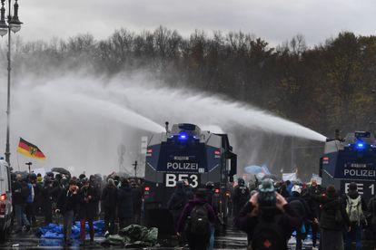A polícia tenta dispersar manifestantes contrários às restrições contra a covid-19 na quarta-feira em Berlim.