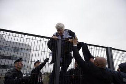 Pierre Plissonnier, com terno e camisa rasgados, tenta saltar uma cerca com a ajuda de agentes.