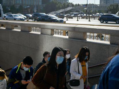 Um grupo de pessoas sai de uma passagem subterrânea em Pequim.