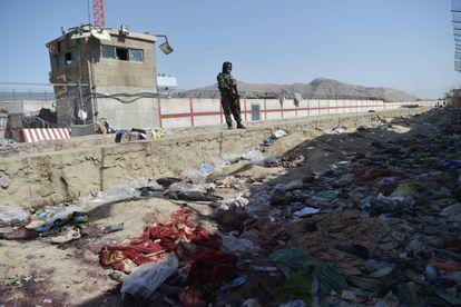 Um talibã monta guarda nesta sexta-feira no local onde um homem-bomba se explodiu, próximo a um portão no aeroporto de Cabul na quinta-feira.