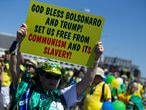"""07 September 2020, Brazil, Brasilia: """"God bless Bolsonaro and Trump! Liberate us from communism and their slavery"""", is written on the poster of a supporter of the right-wing Brazilian president on the Brazilian Independence Day. Photo: Myke Sena/dpa - ATTENTION: For editorial use only and only with full mention of the above credit (Photo by Myke Sena/picture alliance via Getty Images)"""
