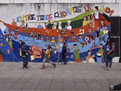Um grupo de crianças brinca no pátio da escola da Virgem del Milagro, em cidade La Cárcova.