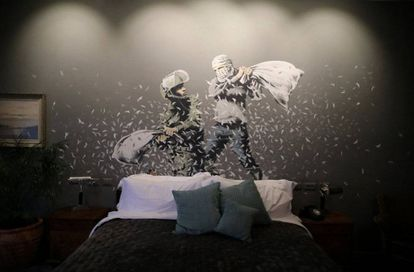 Um dos quartos do Walled Off, decorado com uma obra de Banksy.