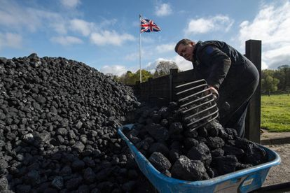Funcionário maneja carvão durante feira de máquinas a vapor em 17 de abril em Hollycoombe (Inglaterra).