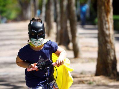 Uma menina protegida com duas máscaras brinca com sua patinete na rua.